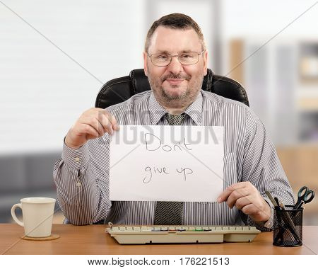 Cheerful male psychotherapist demonstrates written message Do not give up.  Middle-aged man sitting at wooden desk and looks at camera. There are white mug gray keyboard and stationery office items on the desk. Horizontal image on blurred indoor backgroun
