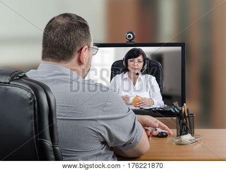 Mature man is ready to insert the syringe into his skin for subcutaneous injection. Telemedicine male patient looks at computer monitor. Virtual female doctor demonstrates how to give it step by step using grapefruit as training arm. Horizontal mid-shot o