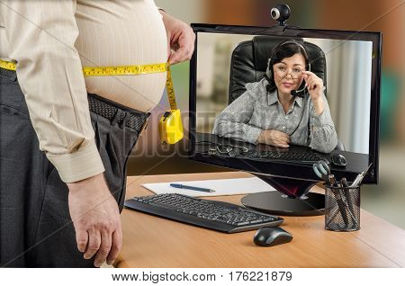Fat businessman measures his body waist by yellow tape meter at workplace in the office. Telemedicine female nutritionist in headset looks at patient belly size on monitor carefully.  Horizontal mid-shot on blurred interior background