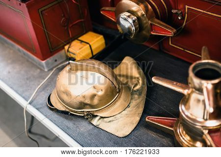 Golden Helmet Of Firefighter On Sidestep Of Fire Truck.