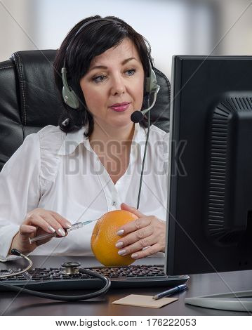 Telemedicine female doctor in headset guides an intramuscular injection by internet.  Mature woman sits opposite desktop monitor and makes clear to someone technique with syringe and grapefruit. Vertical mid-shot on blurred indoors background
