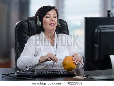 Telecare female doctor gives an explanation of subcutaneous injection technique using grapefruit.  Mid aged confident woman inserts syringe into the peel. Virtual doc in headset sits in front of computer monitor at black desk. Horizontal mid-shot on blurr
