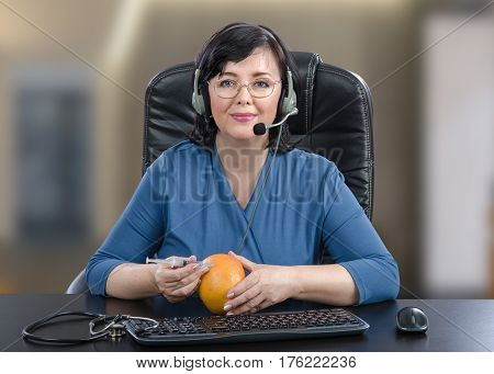 Telemedicine doctor in headset makes clear how to administer an intramuscular injection by grapefruit as training arm. Confident woman sits in tall office chair at black desk looking at the camera