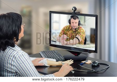 Virtual female doctor has just made clear how to make an intravenous injection with training arm and now conducts telehealth patient in monitor. Mature man in aloha shirt is ready to administer medication into his vein. Horizontal mid-shot on blurred indo