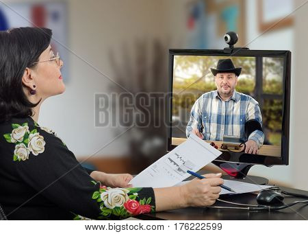 Telemedicine doctor reviews blood pressure graph with farmer man. Middle-aged cowboy in checkered shirt, black hat takes his blood pressure in monitor at the same time. Horizontal mid-shot on blurred interior background