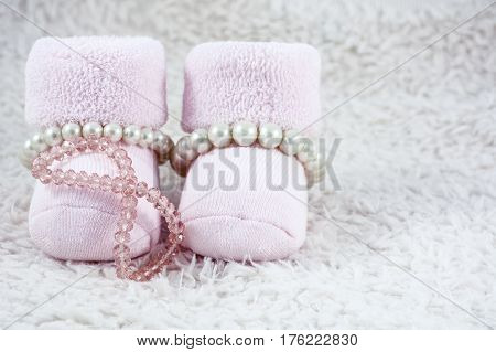 Pink booties for babies with several pink bracelets on the white fur