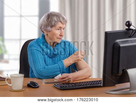 Aged woman administers an intramuscular injection in front of monitor under telemedicine manual services