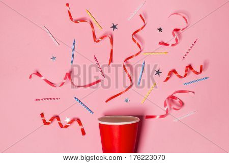 Flat lay of Celebration. Paper cup with colorful party streamers on pink background.