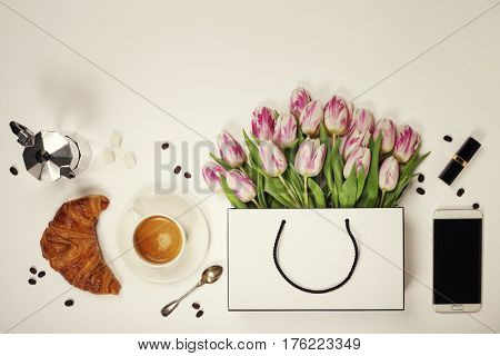 Top view of spring flowers, coffee, mobile phone, croissant and cosmetics. Flat lay image. Holiday, romance of modern life concept