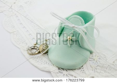 Blue baby fondant sugar bootee on white lace background with silver charms - baby shower