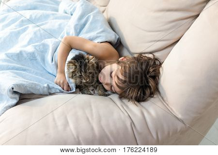 Child sleeping with cat at home
