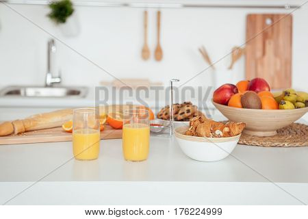 Plate of tasty cookies with chocolate crumbs, croissant, baget, bananas, apples, persimmon, orange and orange juice on white table.