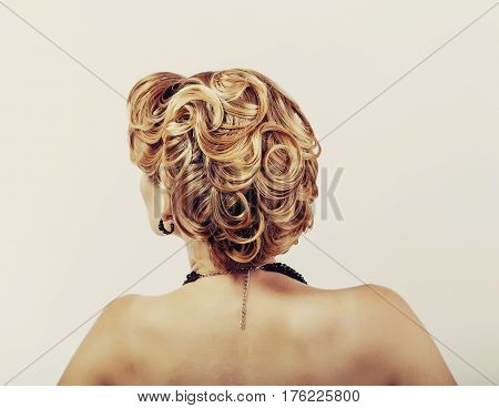 beautiful woman with blond hair wearing little black dress touching her neck view from the back on white.