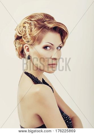 Beautiful blonde woman in elegant black low cut back evening dress with updo hairstyle. Front view isolated on white background.