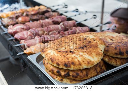 Raw kebab and pitas grilling on metal skewer. Chicken and meat roasting at barbecue. BBQ fresh beef chop slices. Traditional eastern dish, shish kebab. Grill on charcoal and flame, picnic, street food