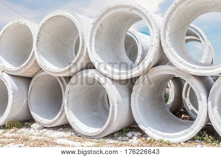 Pile of big concrete drainage pipes with construction site background.