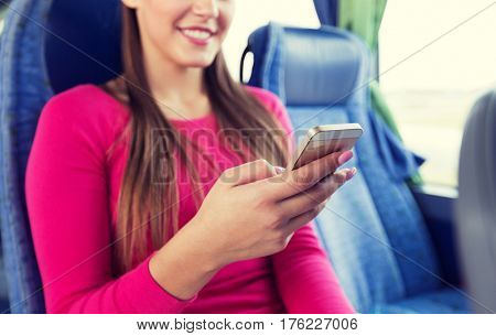 transport, tourism, road trip and people concept - close up of woman in travel bus texting or reading message on smartphone