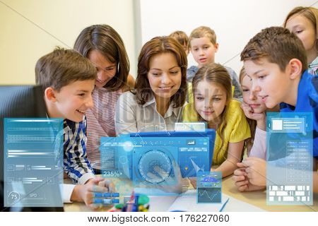 education, elementary school, learning, technology and people concept - group of kids with teacher looking to tablet pc computer in classroom and virtual screen projection
