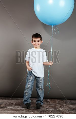 Full length of smiling little boy holding blue balloon over grey background