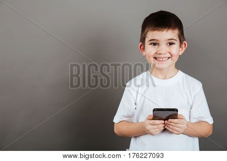 Cheerful little boy standing and using cell phone over grey background