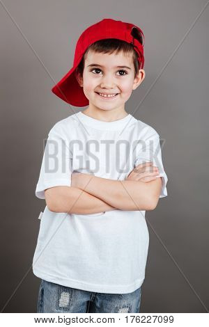 Smiling little boy in red cap standing with hands folded over grey background