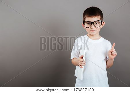 Cute little boy in glasses holding blank magazine and showing thumbs up over grey background