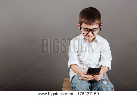 Cheerful little boy in glasses sitting and using smartphone over grey background
