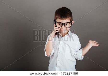 Happy little boy in glasses talking on mobile phone and holding copyspace on palm over grey background