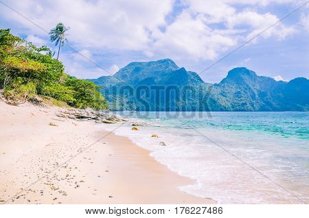 Stunning beach on Helicopter Island in the Bacuit archipelago in El Nido, Cadlao Island in Background, Palawan, Philippines.