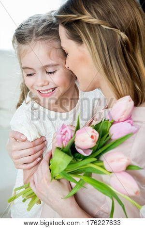 Side View Of Happy Mother With Tulips Hugging Smiling Daughter, Mother's Day Concept