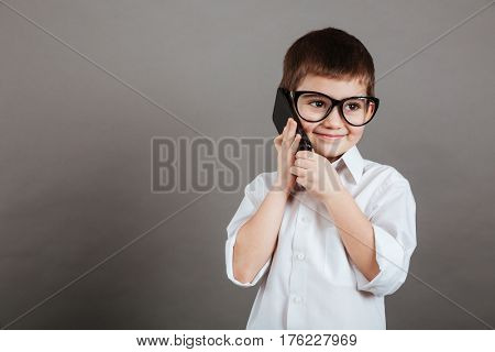 Cheerful little boy businessman in glasses talking on cell phone over grey background
