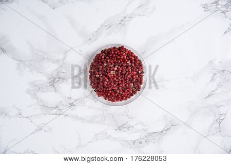 Top view of a red pepper in a bowl on white marble table