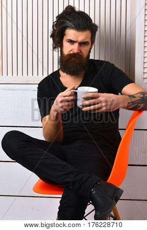Bearded man long beard. Brutal tattooed caucasian hipster with moustache holding cup or mug in rock black style sitting on acid orange chair on white wooden vintage studio background