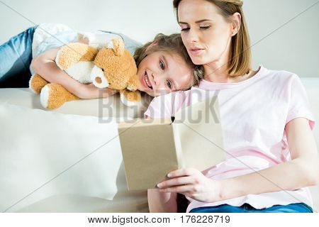 Smiling Mother And Daughter With Teddy Bear Reading Book Together On Sofa