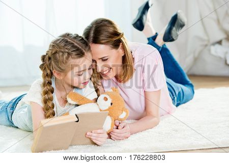 Happy Mother And Daughter With Teddy Bear Reading Book On Carpet