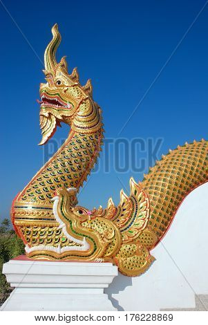Golden serpent king or king of naga statue in Thai temple on clear blue sky background