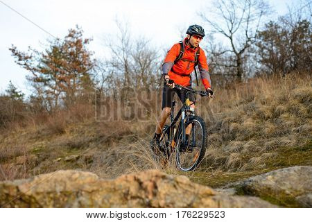 Enduro Cyclist Riding the Mountain Bike on the Rocky Trail. Extreme Sport Concept. Free Space for Text.