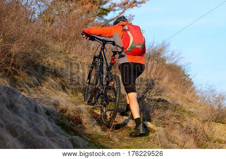 Enduro Cyclist Taking his Mountain Bike Up the Rocky Trail. Extreme Sport Concept. Free Space for Text.