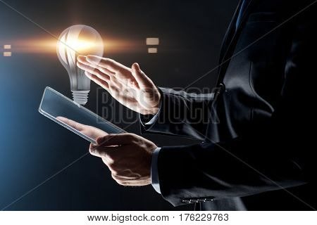business, people and future technology concept - close up of businessman hands with transparent tablet pc computer and lightbulb projection over black background