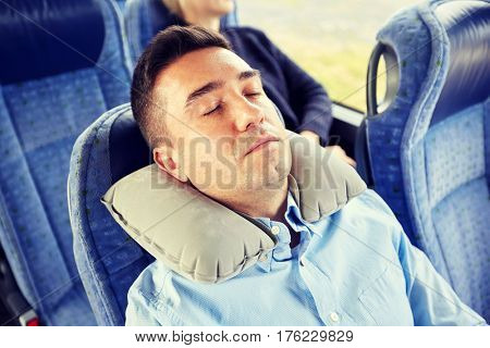transport, tourism, rest , comfort and people concept - man sleeping in travel bus or train  with cervical neck inflatable pillow
