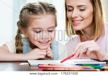 Happy Mother And Daughter Drawing At Home
