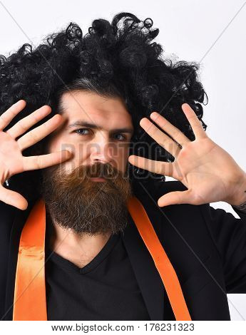Bearded man long beard. Brutal caucasian hipster with moustache have acid orange tie on suit and black curly afro wig isolated on white studio background