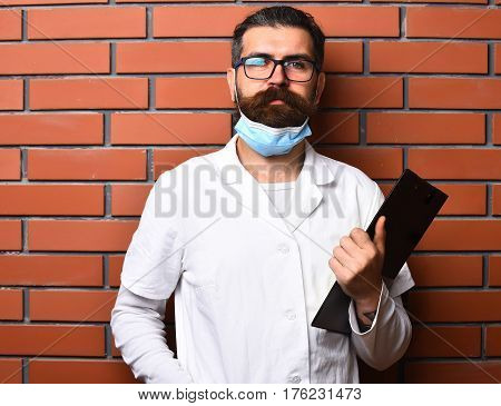Bearded man long beard. Brutal caucasian doctor or unshaven hipster postgraduate student holding clipboard in medical gown and mask on brown brick wall studio background. Medicine concept