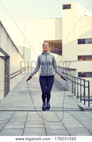 fitness, sport, people, exercising and lifestyle concept - happy woman skipping with jump rope outdoors