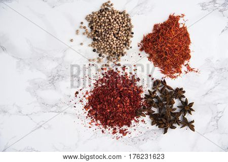 Top view of anise, white pepper, chilli pepper flakes and saffron heaps isolated on white marble background