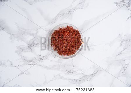 Top view of dried saffron in small bowl isolated on white marble table