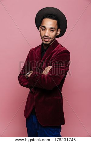 Portrait of a handsome stylish afro american man in jacket and hat standing with arms folded isolated on the pink background