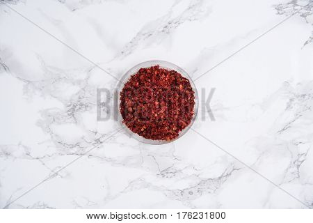 Top view of dried chilli pepper in small bowl isolated on white marble table