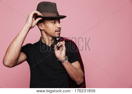 Portrait of a young handsome afro american man in hat holding jacket over shoulder isolated on the pink background