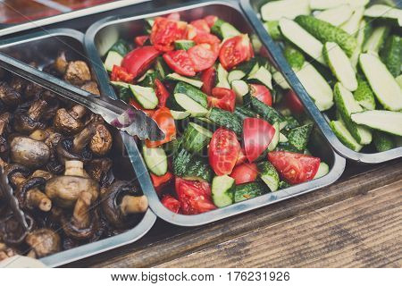 Sandwich bar salads choice in metal containers. Different fillings - grilled mushrooms, sliced onions, tomatoes, cucumbers for fast food take away in cafe. Vendor's equipment for street meal.